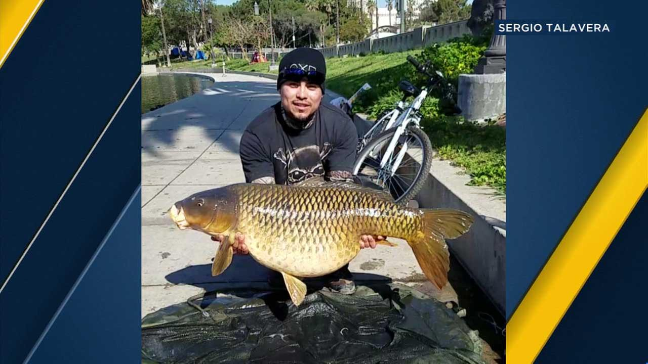 Enrique Salmeron holds up a 50-pound fish caught at MacArthur Park Lake on Monday, March 27, 2017.