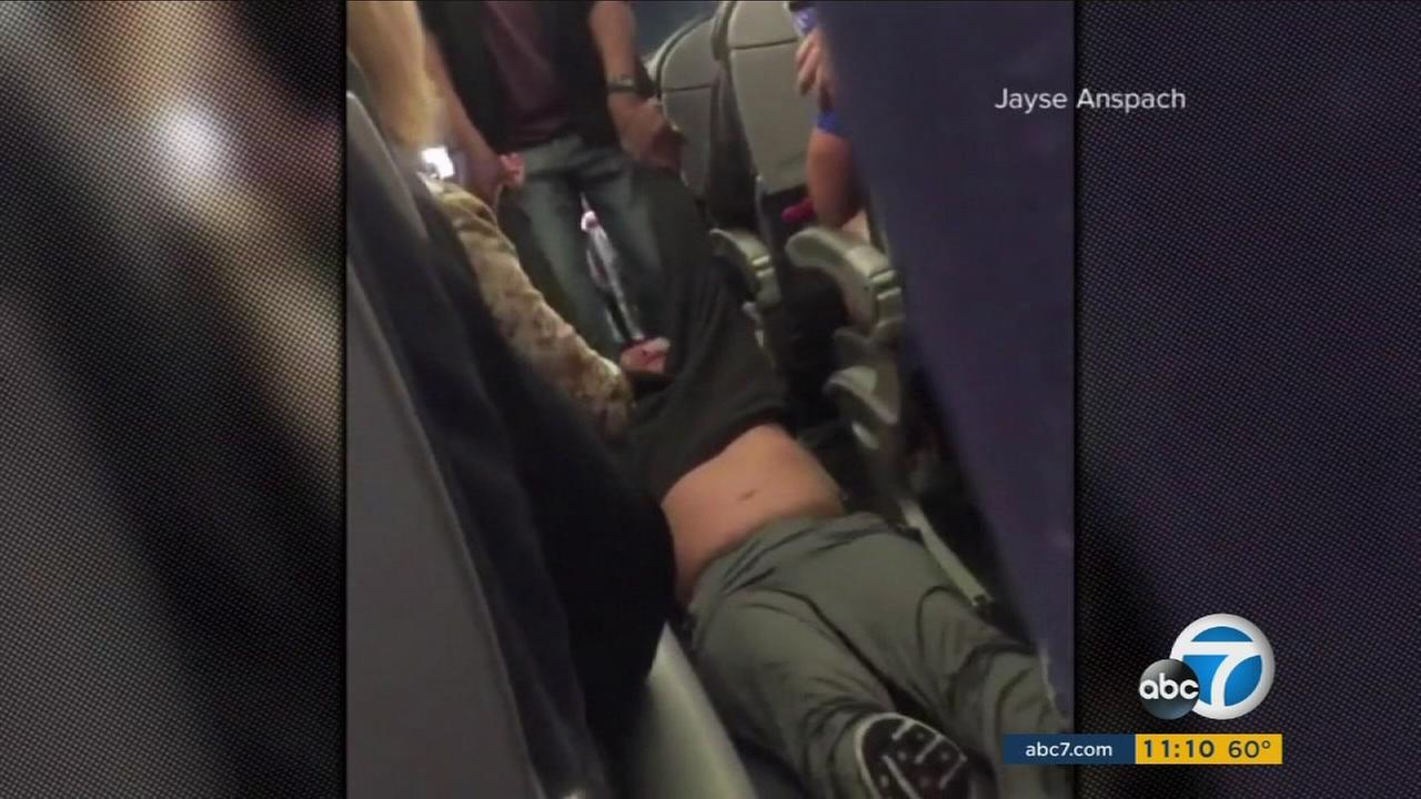 Video shows three security officials dragging a male passenger from a United Airlines flight that the airline said was overbooked as it waited to depart from Chicagos OHare International Airport.
