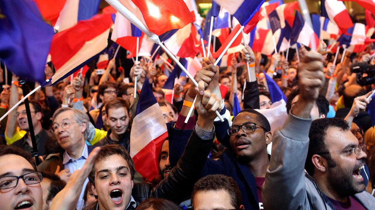 Supporters of French presidential candidate Emmanuel Macron react as the first partial official results and polling agencies projections are announced on Sunday, April 23, 2017.