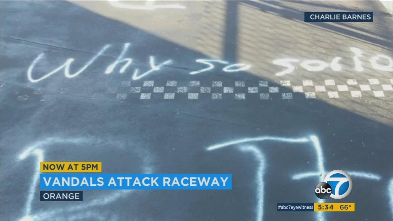 Vandalism and spray painted words are shown on a remote control race car track in Orange.