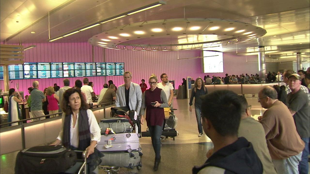 Travelers enter a terminal at Los Angeles International Airport after returning from London.