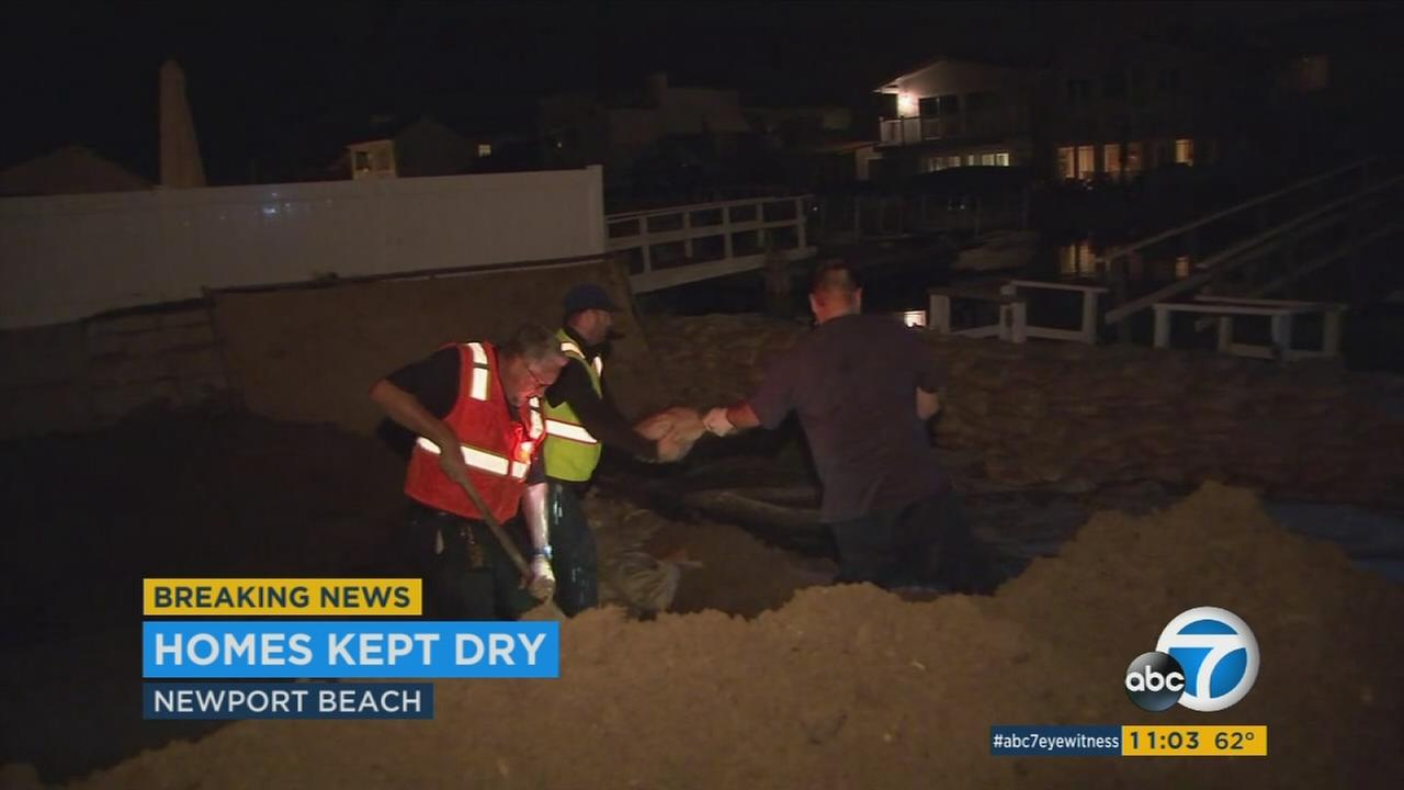 Newport Beach officials and city residents work to keep homes dry during a high tide on Thursday, May 25, 2017.