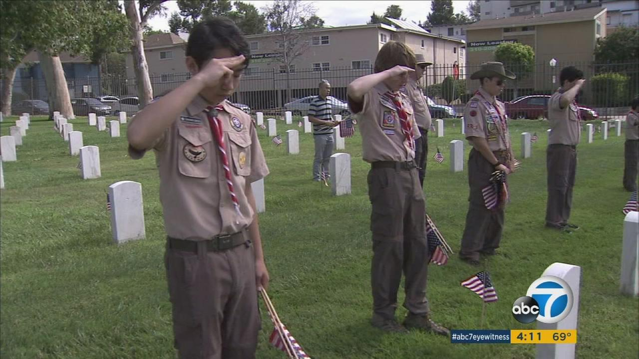 Boy Scouts salute fallen soldiers graves after marking it with an American flag in honor of Memorial Day at the Los Angeles National Cemetery on Saturday, May 27, 2017.