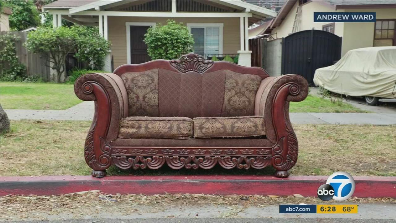 An abandoned sofa is shown along the curb of a neighborhood and is part of Andrew Wards photography exhibit.