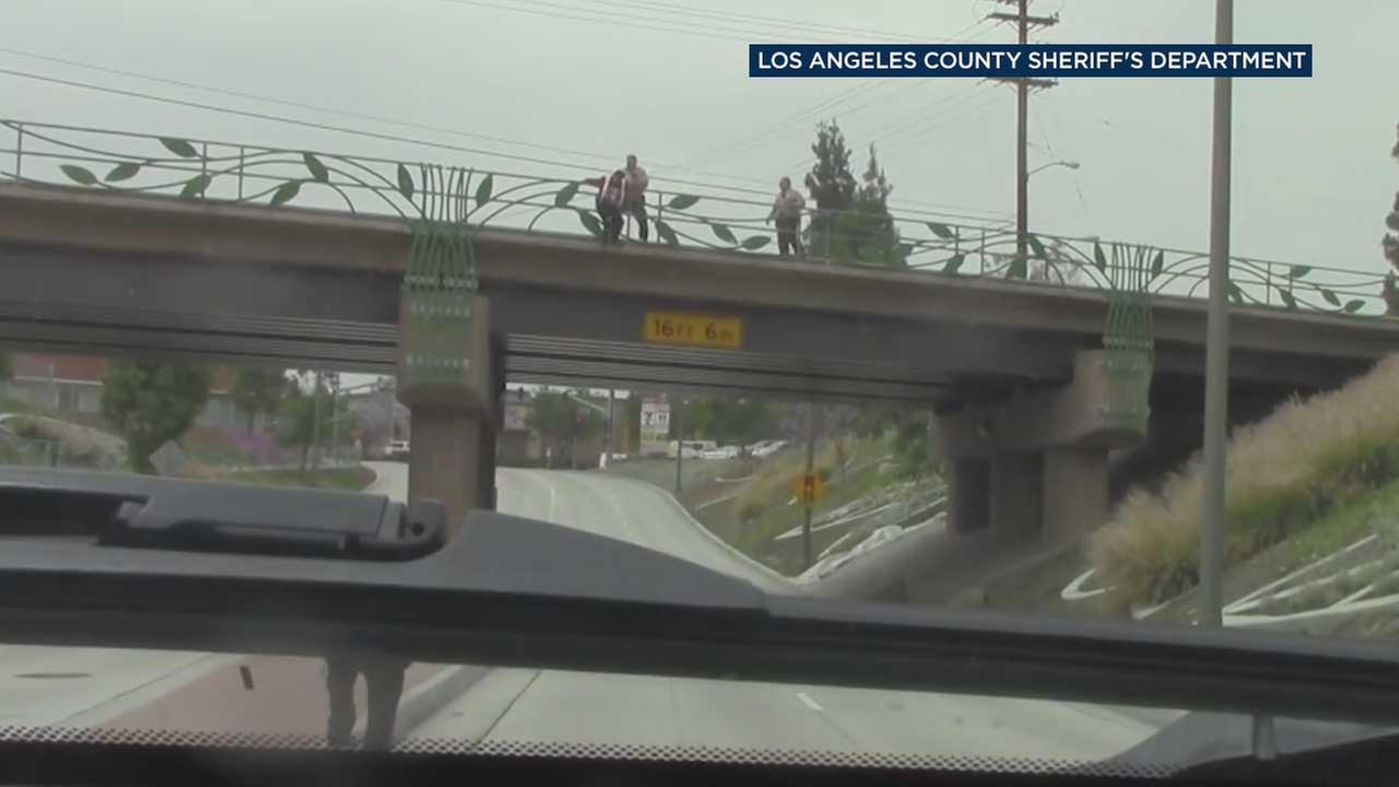 Two Los Angeles County Sheriffs Department deputies are seen approaching a teenager who threatened to jump off a railroad bridge in Pico Rivera on Tuesday, May 20, 2017.