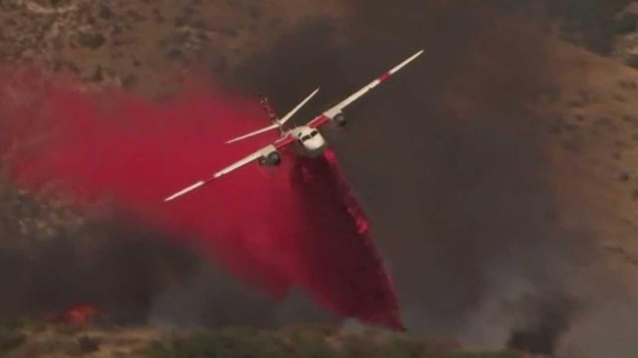 An aircraft drops fire retardant as a wildfire burns in the Inland Empire community of Highland on Tuesday, June 27, 2017.