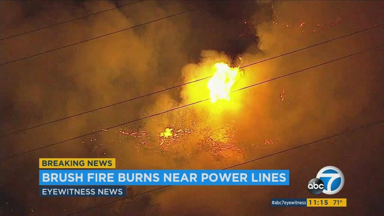 A brush fire that erupted in a hillside above Claremont threatened structures and power lines Thursday before it was brought under control.