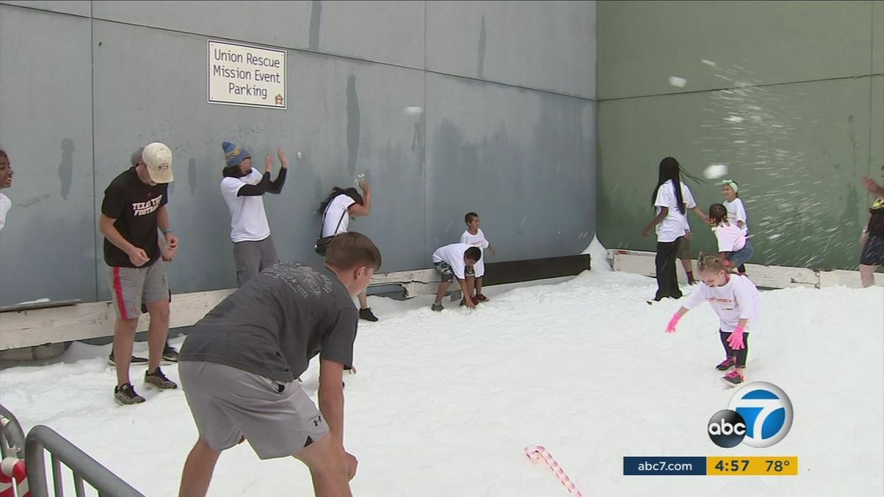 Kids and parents play in snow as part of a Christmas in July celebration at the Union Rescue Mission in Skid Row.