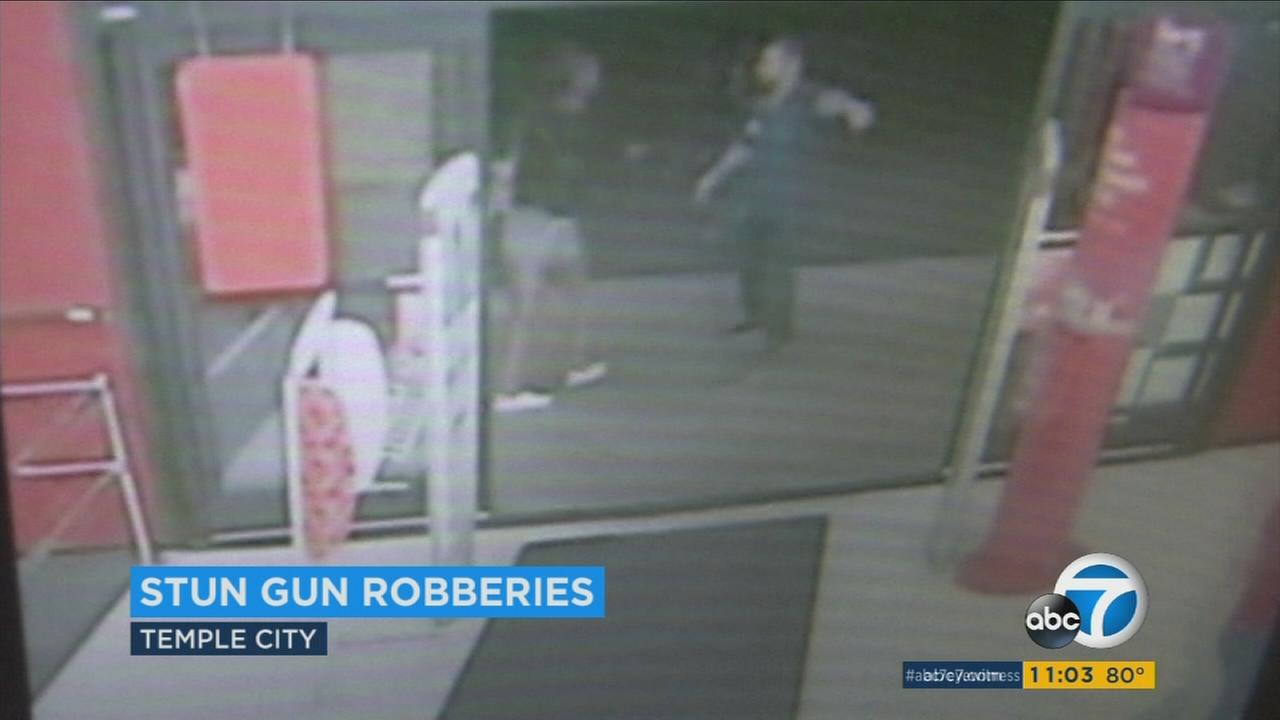 A surveillance image shows a female suspect point a stun gun at a CVS employee in Temple City on Thursday, July 13, 2017.