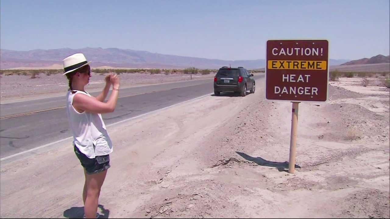 A woman snaps a photo of a sign posted in the Death Valley area.