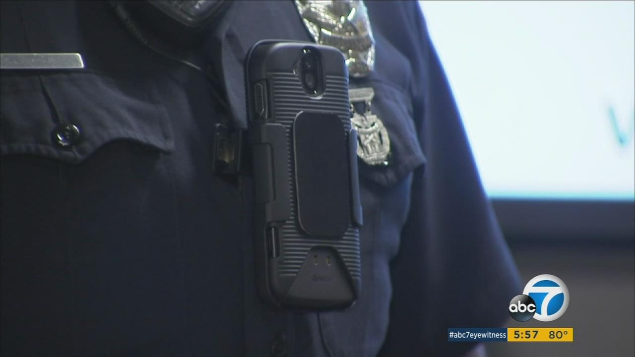 A body camera on a police officer is shown.
