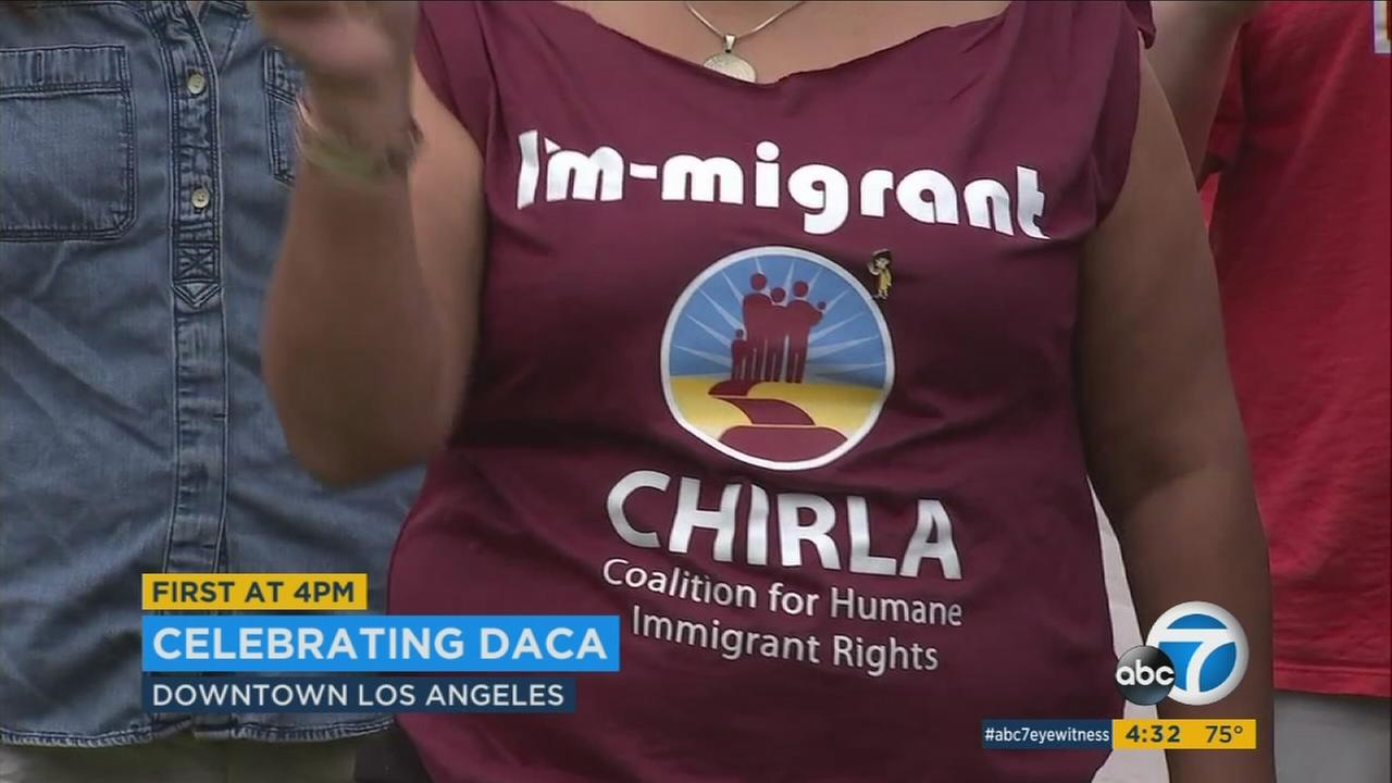 A woman wears an Im - migrant shirt at a DACA anniversary celebration and defense of the program in downtown Los Angeles.