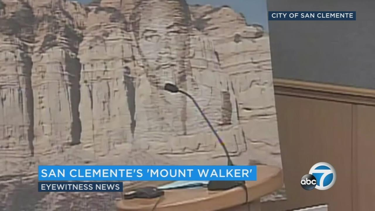 A Paul Walker fan holds a mockup of a proposed Mount Rushmore-style memorial to the actor on a San Clemente cliffside.