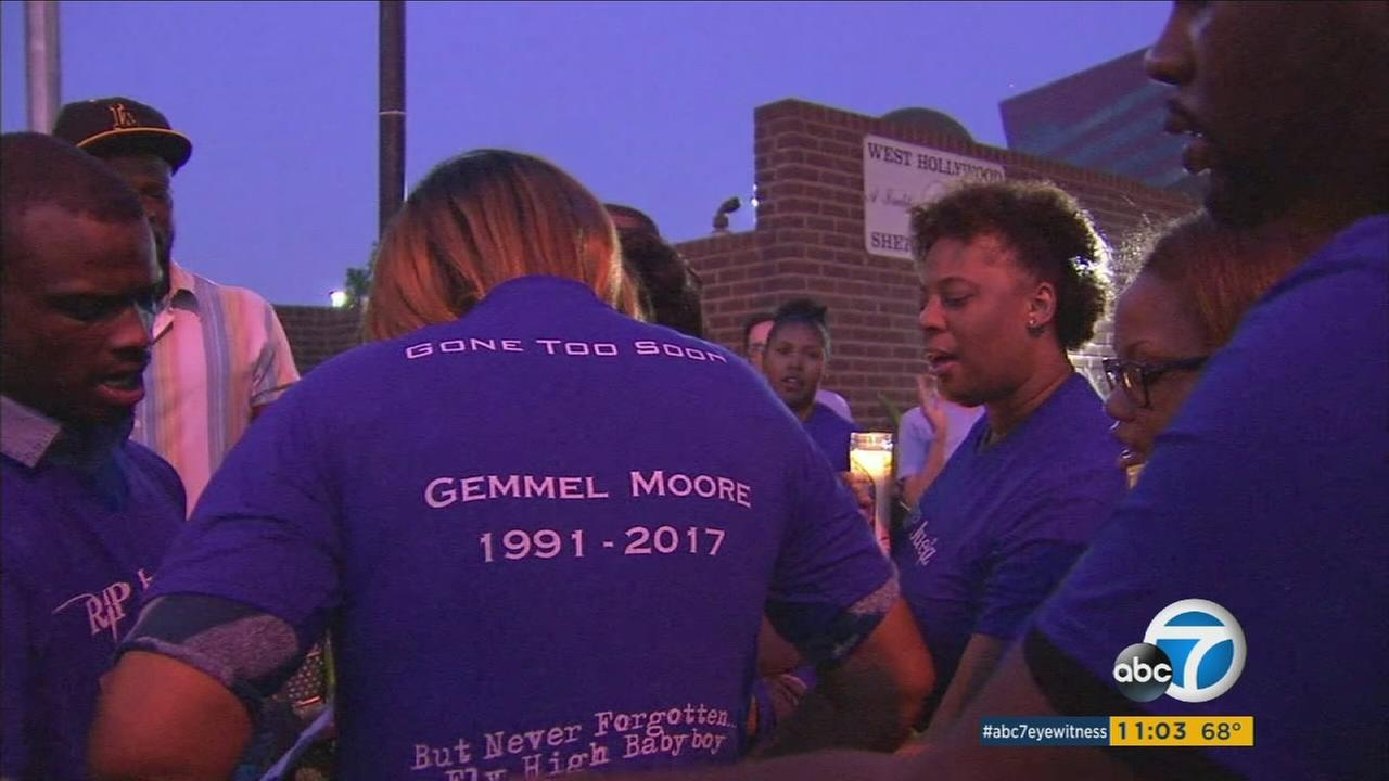 A woman is seen putting on a shirt with the birth date and death date of Gemmel Moore.