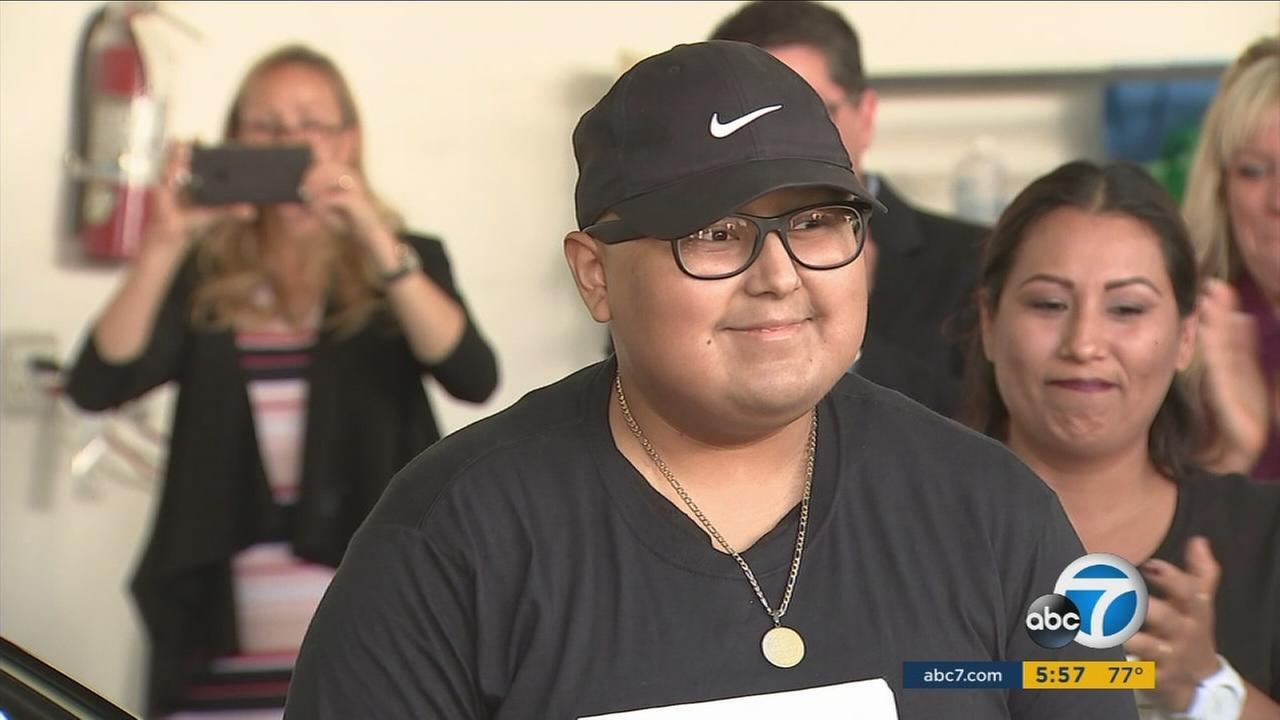 Diego Jimenez, 14, smiles as he and his family members are presented with a new car.
