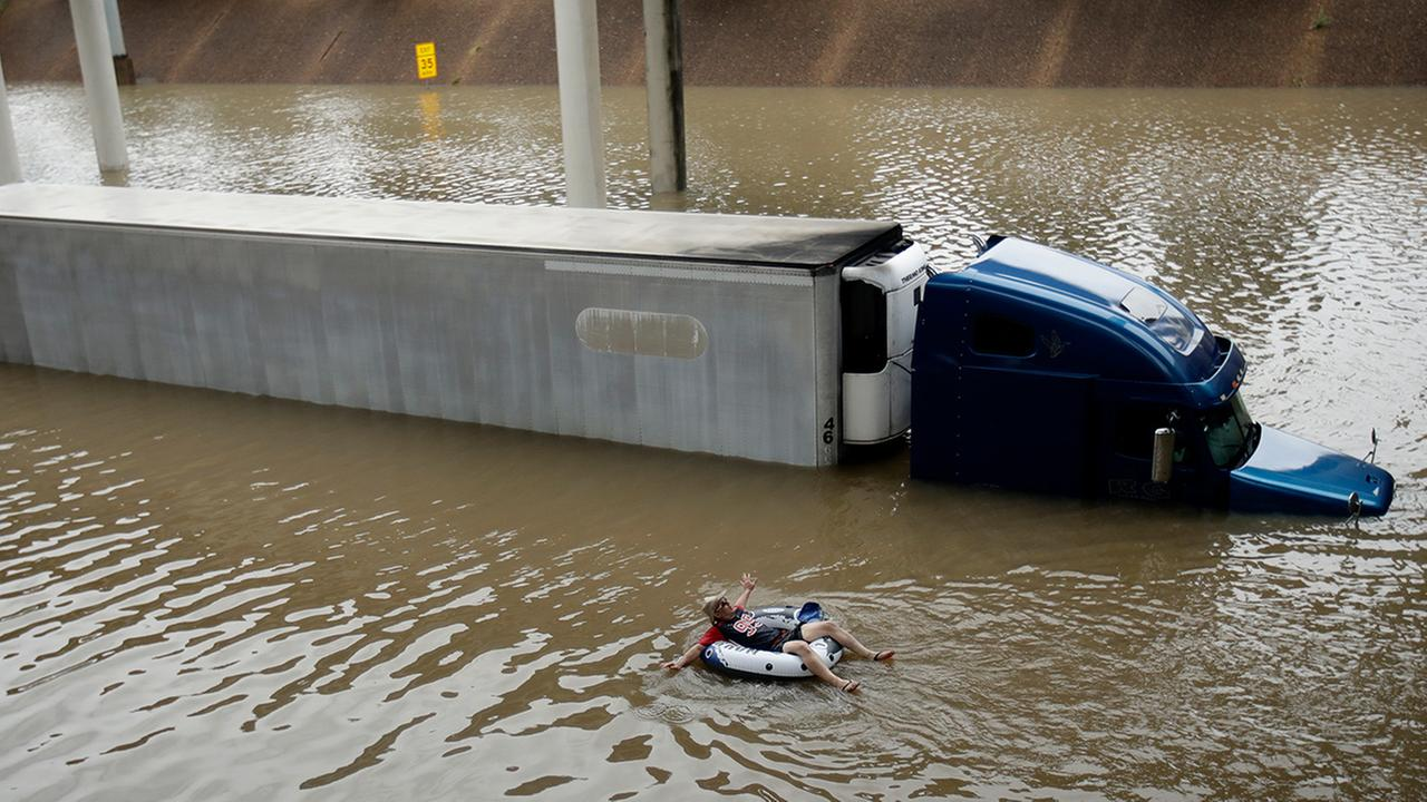 After helping the driver of the submerged truck get to safety, a man floats on the freeway flooded by Tropical Storm Harvey on Sunday, Aug. 27, 2017, near downtown Houston.