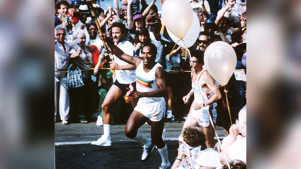 American athlete O.J. Simpson runs with the Olympic torch as the crowd cheers in downtown Los Angeles, Ca., on July 21, 1984.