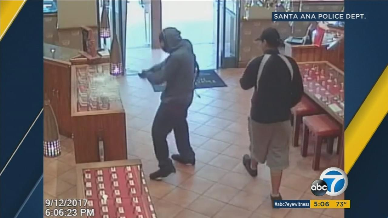Surveillance video released by Santa Ana police shows a man walking into a jewelry store as the man behind him, wearing a mask, begins to smashing a case with a crowbar.