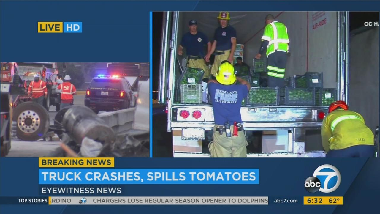 Crews work to clean up the scene of a big rig crash that led to a fuel spill and tomatoes on the 5 Freeway in San Clemente on Monday, Sept. 18, 2017.