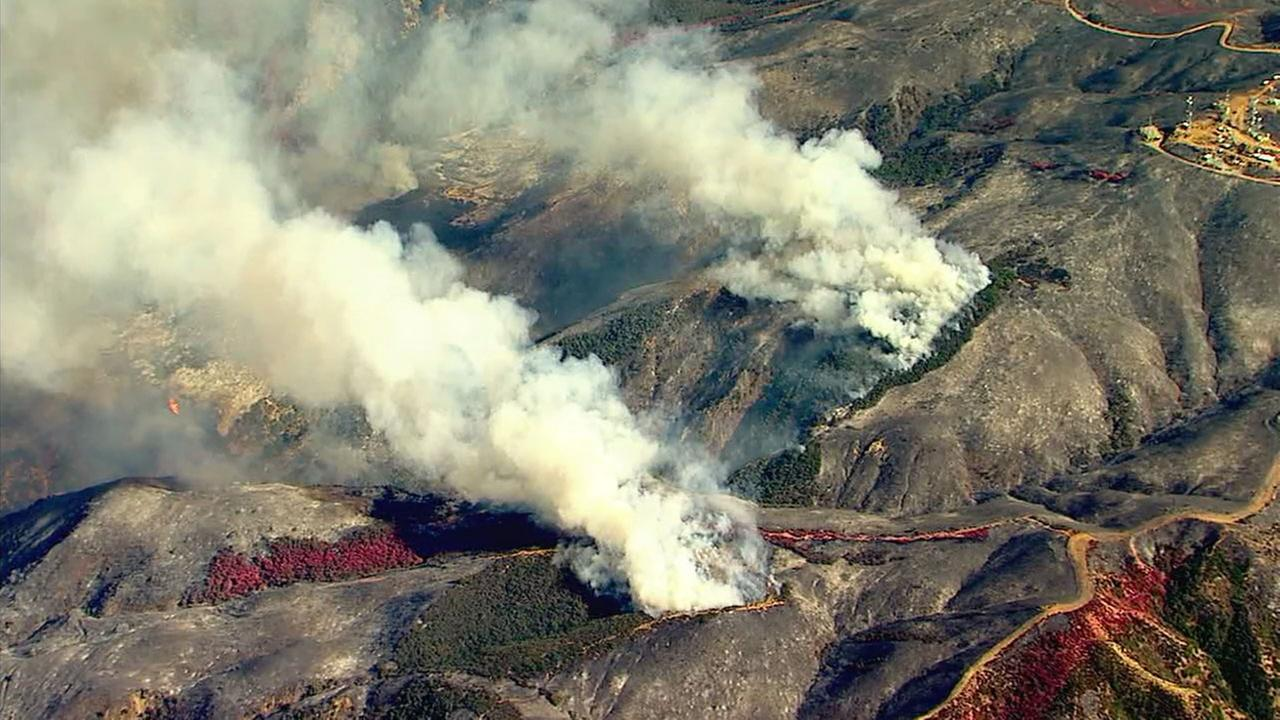 Plumes of smoke billowed from the hillsides bordering Anaheim and Corona as a brush fire continued to burn in the area on Tuesday, Sept. 26, 2017.