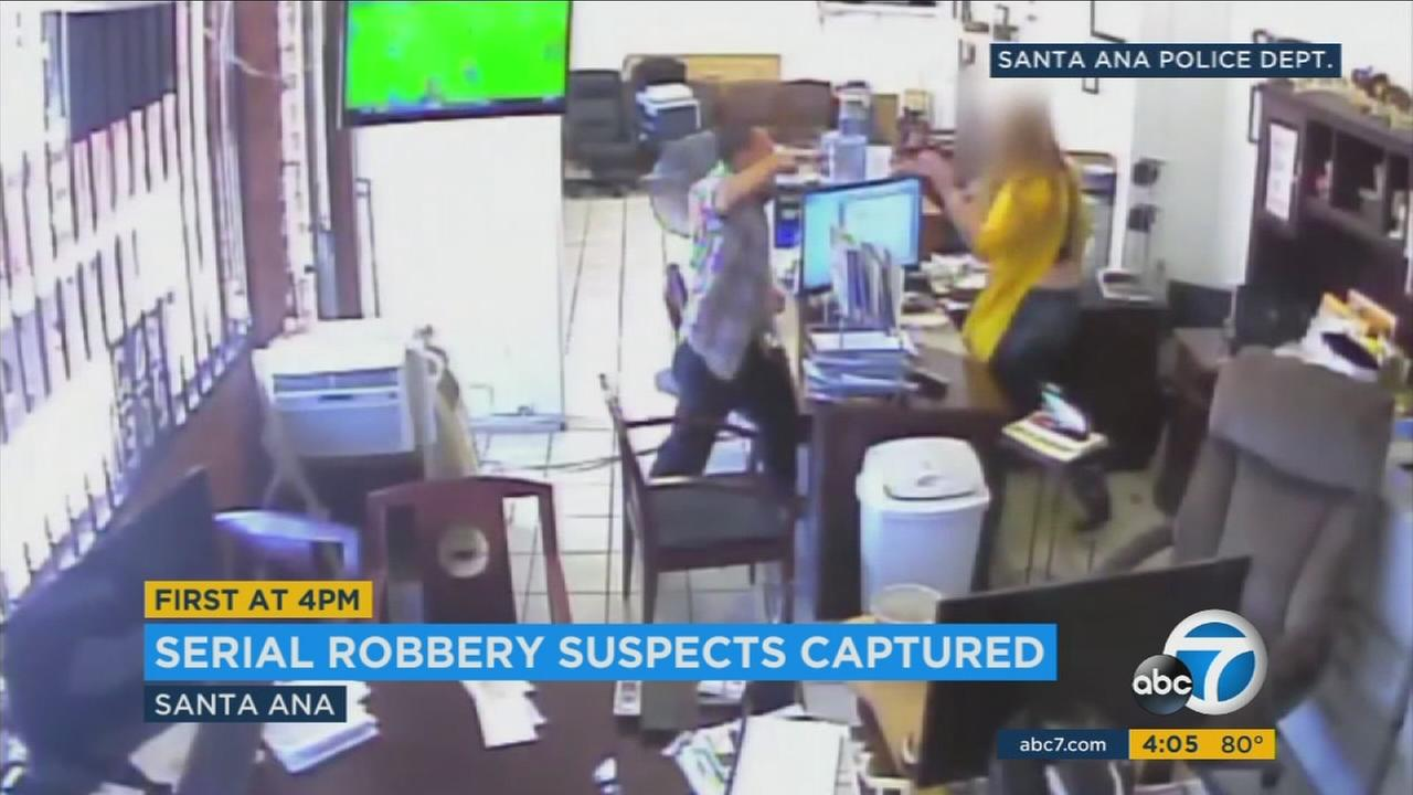 Surveillance video shows an armed robbery suspect, an identical twin, holding up an employee at a business in Santa Ana.