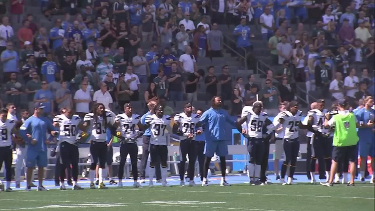 A row of L.A. Chargers players lock arms during the national anthem, ahead of their game on Sunday, Oct. 1, 2017.