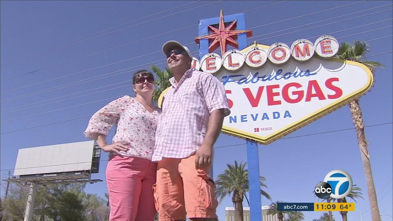 A couple take a photo in front of the famous Las Vegas, Nevada sign.