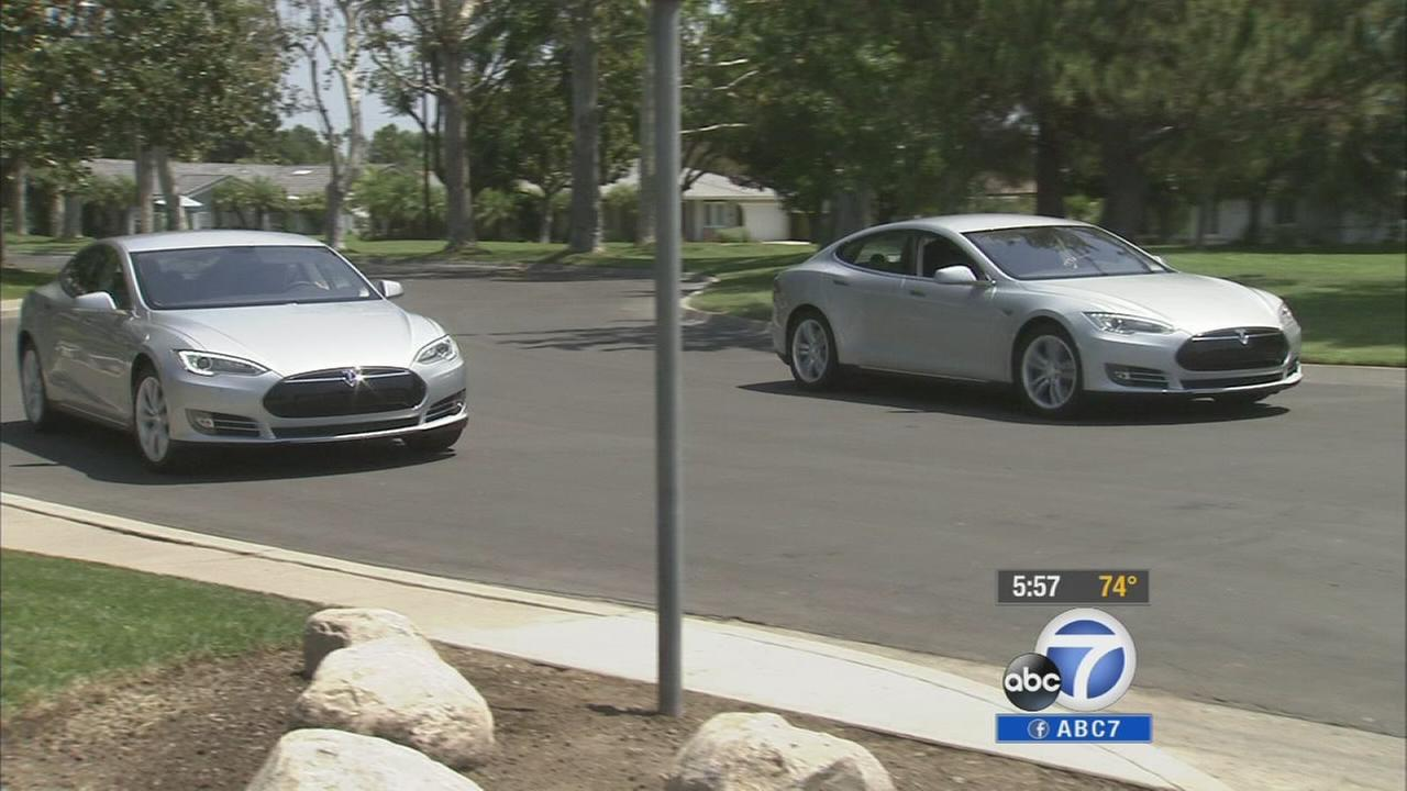 The Briscos drive in his and hers Teslas in this undated file photo.