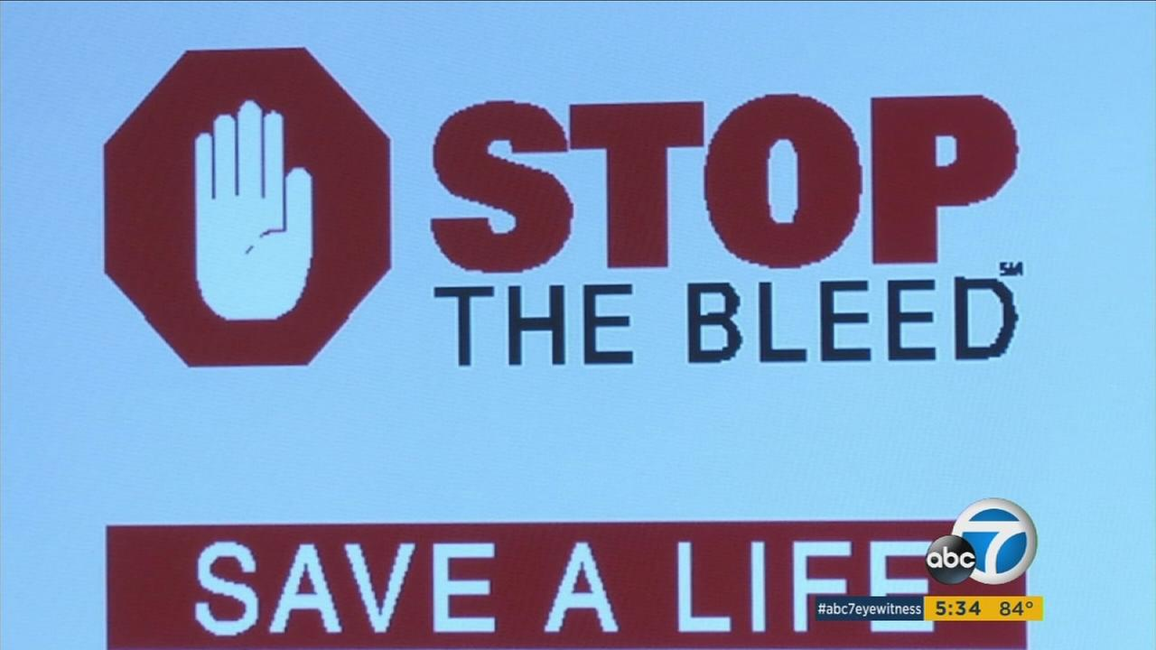 An image shows a digital sign about the Stop the Bleed program held by UCI Medical Center staff to teach civilians and first responders how to stop severe bleeding.