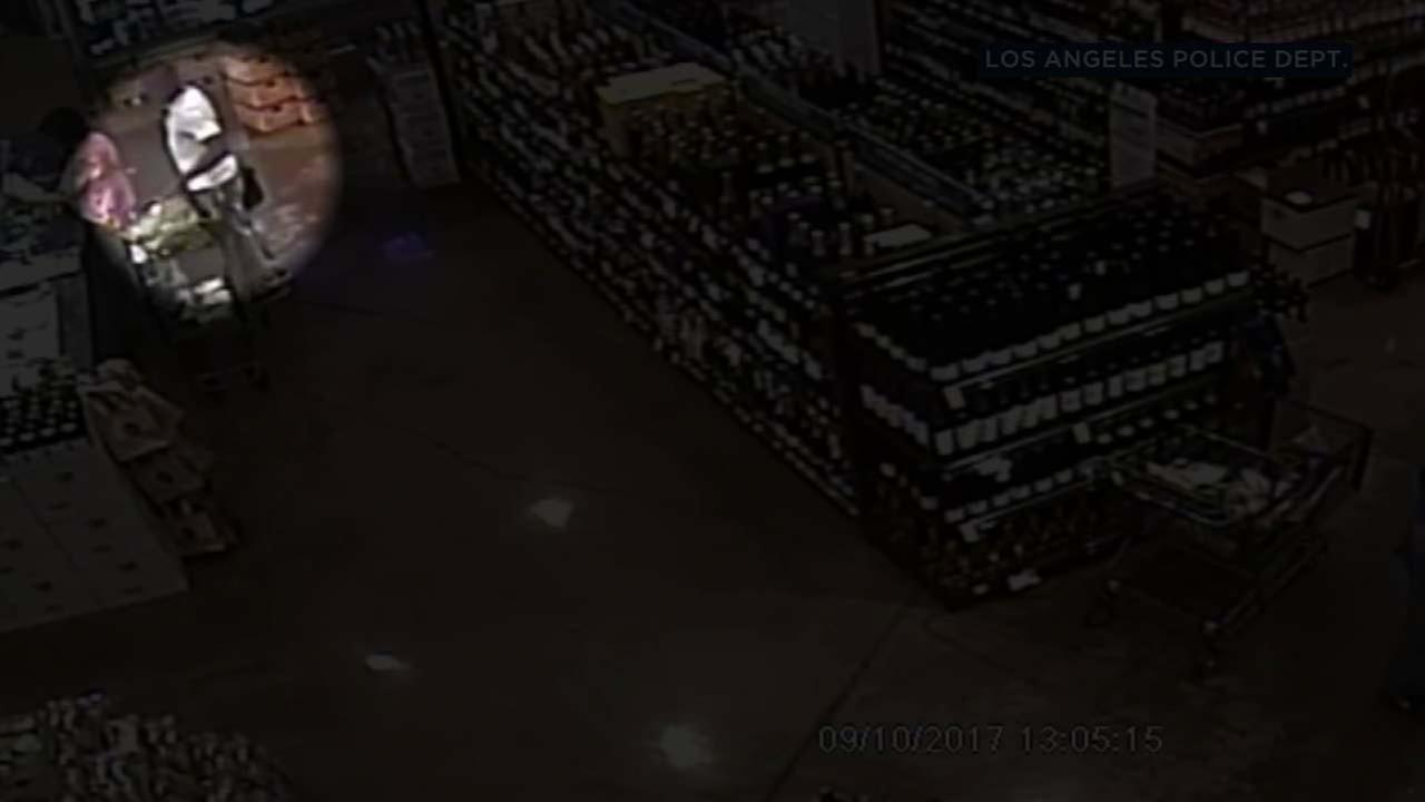 A suspect is seen taking a wallet from a womans purse at a grocery store in the Fairfax District in surveillance video released by the LAPD.
