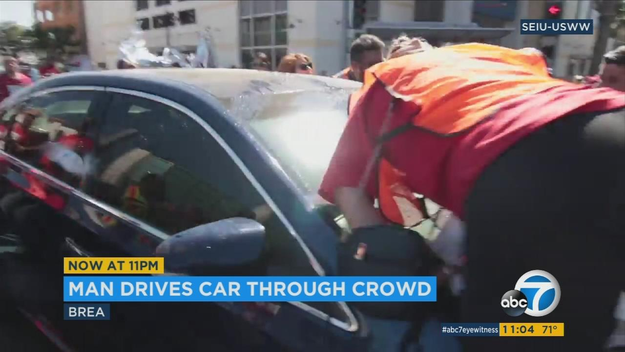 A group of protesters outside U.S. Rep Ed Royces office are seen getting on top of a car as it tries to move through an intersection in Brea.