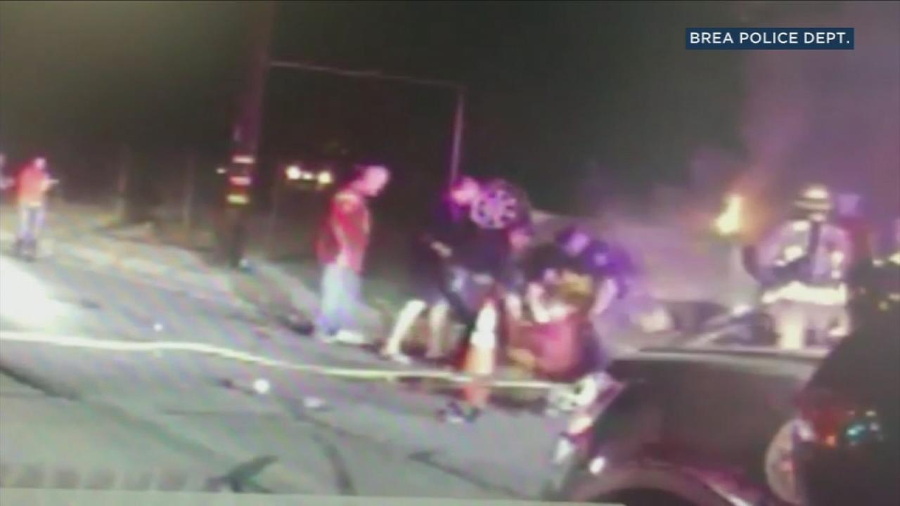 Dashcam video from a police officers patrol vehicle shows him and four others rescuing a man in a burning, overturned vehicle in Brea.