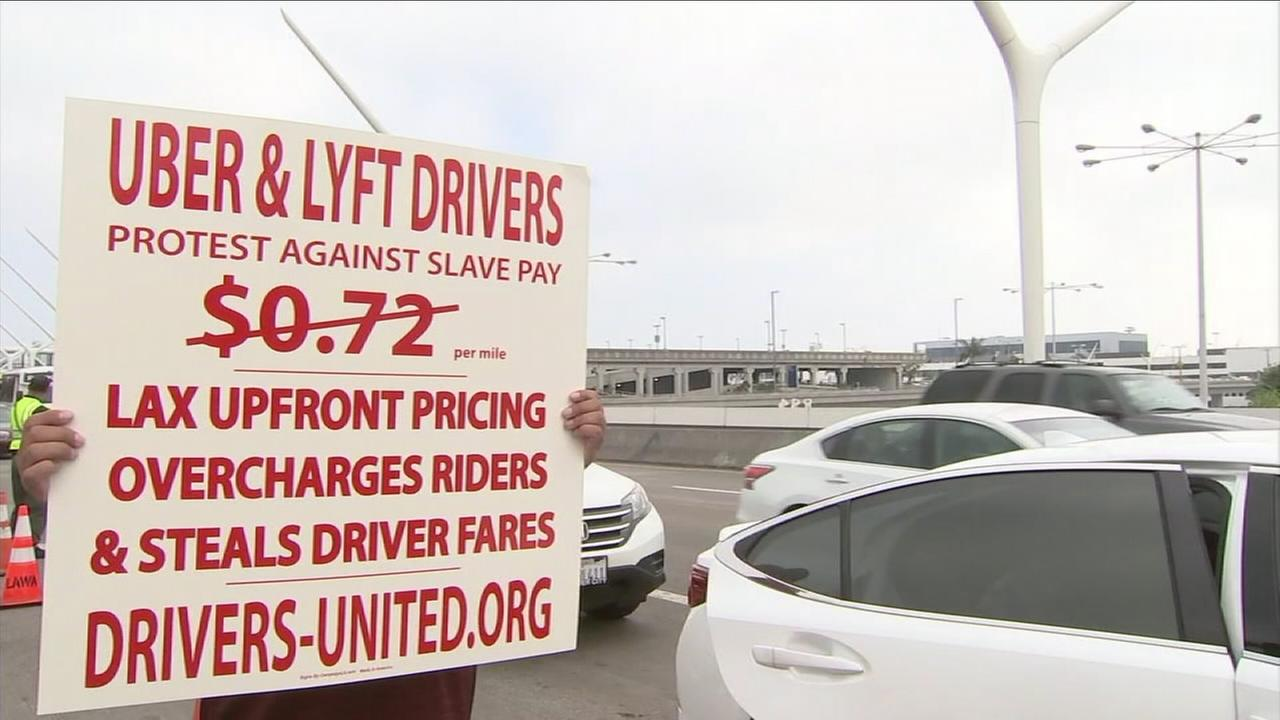 A rideshare driver holds a sign demanding higher wages from either Uber or Lyft while at Los Angeles International Airport on Sunday, Nov. 26, 2017.