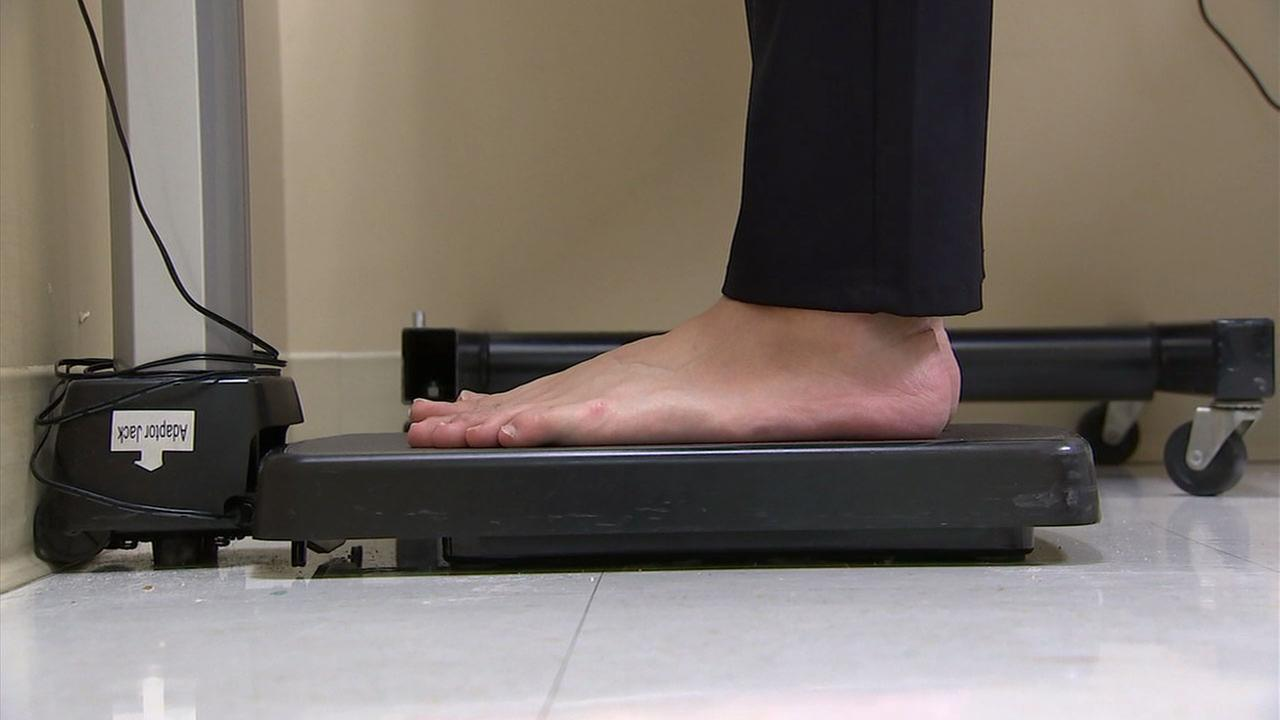 A person is shown standing on a scale at a doctors office.