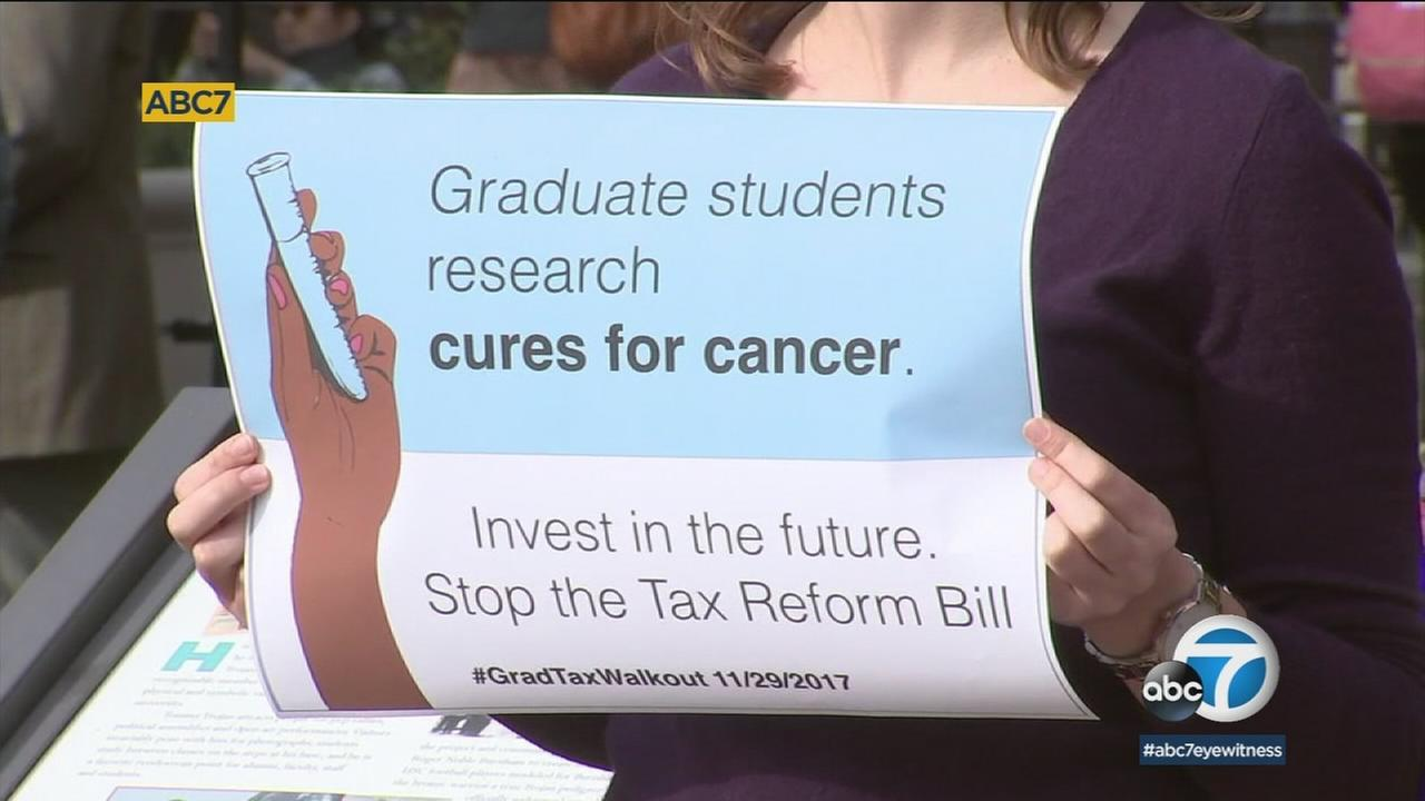 A graduate student at USC holds a sign protesting the GOP tax reform bill that has been proposed in Congress.