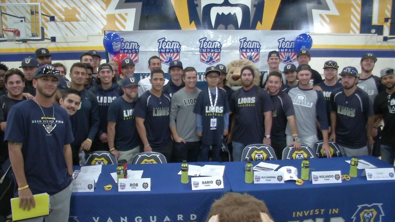 Dario Teran, 8, takes a photo with the Vanguard University baseball team during a press conference on Wednesday, Nov. 29, 2017.
