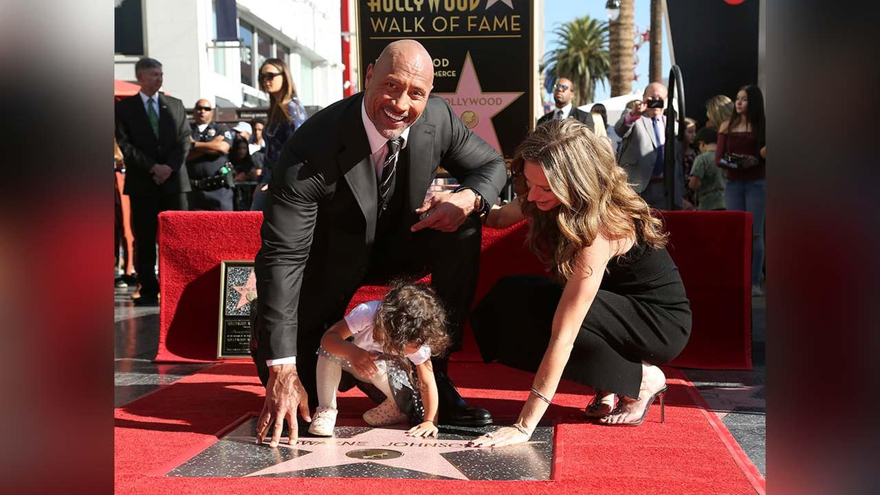 Dwayne Johnson, Lauren Hashian and their daughter pose for a photo at a ceremony honoring him with a star on the Hollywood Walk of Fame Wednesday, Dec. 13, 2017, in L.A.