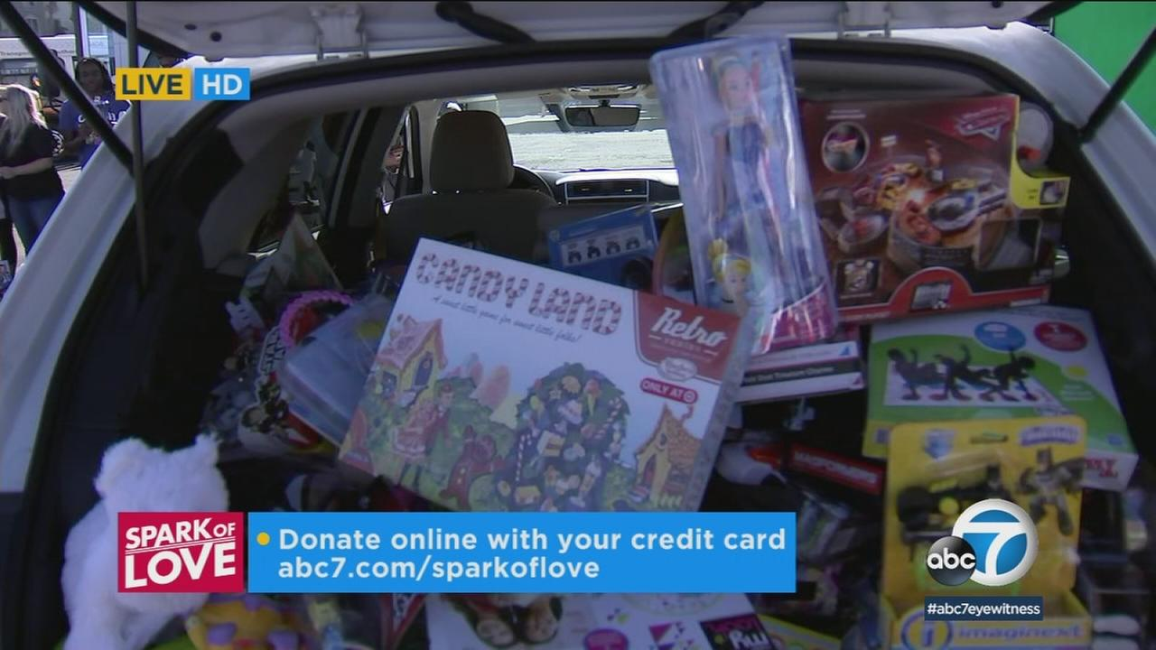 Multiple businesses and community organizations showed up at Fridays Spark of Love toy drive with carloads of gifts for kids.