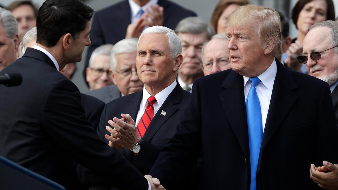 President Donald Trump shakes hands with House Speaker Paul Ryan of Wis., as Vice President Mike Pence watches, at the White House, Wednesday, Dec. 20, 2017, in Washington.