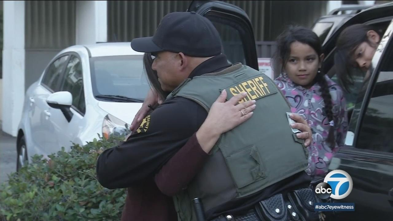 An Orange County sheriffs deputy gave a stranger a hug after gifting them for the holiday season in San Clemente on Wednesday, Dec. 20, 2017.