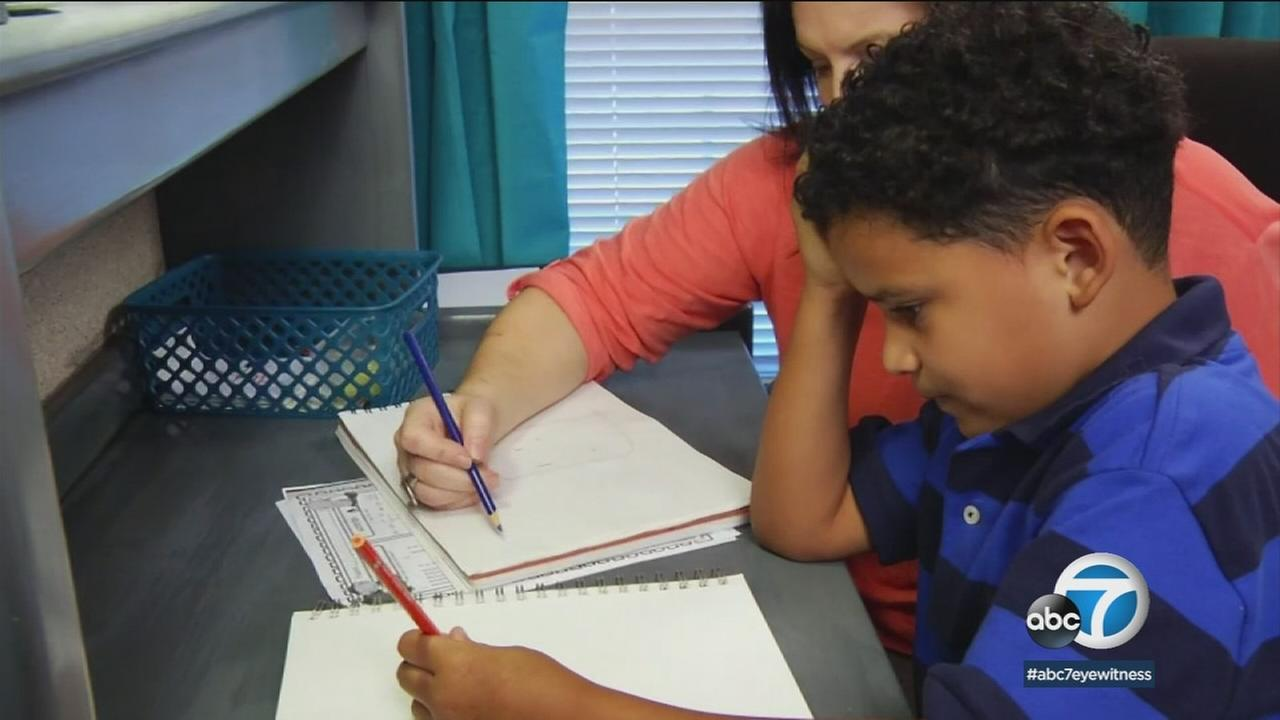 A child who has autism and ADHD is shown learning in a photo.