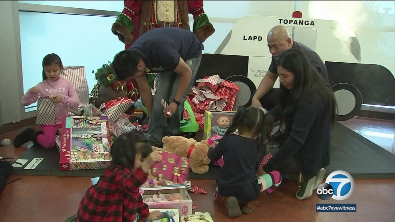Three young girls open presents with their family thanks to the kindness of some Los Angeles police officers.