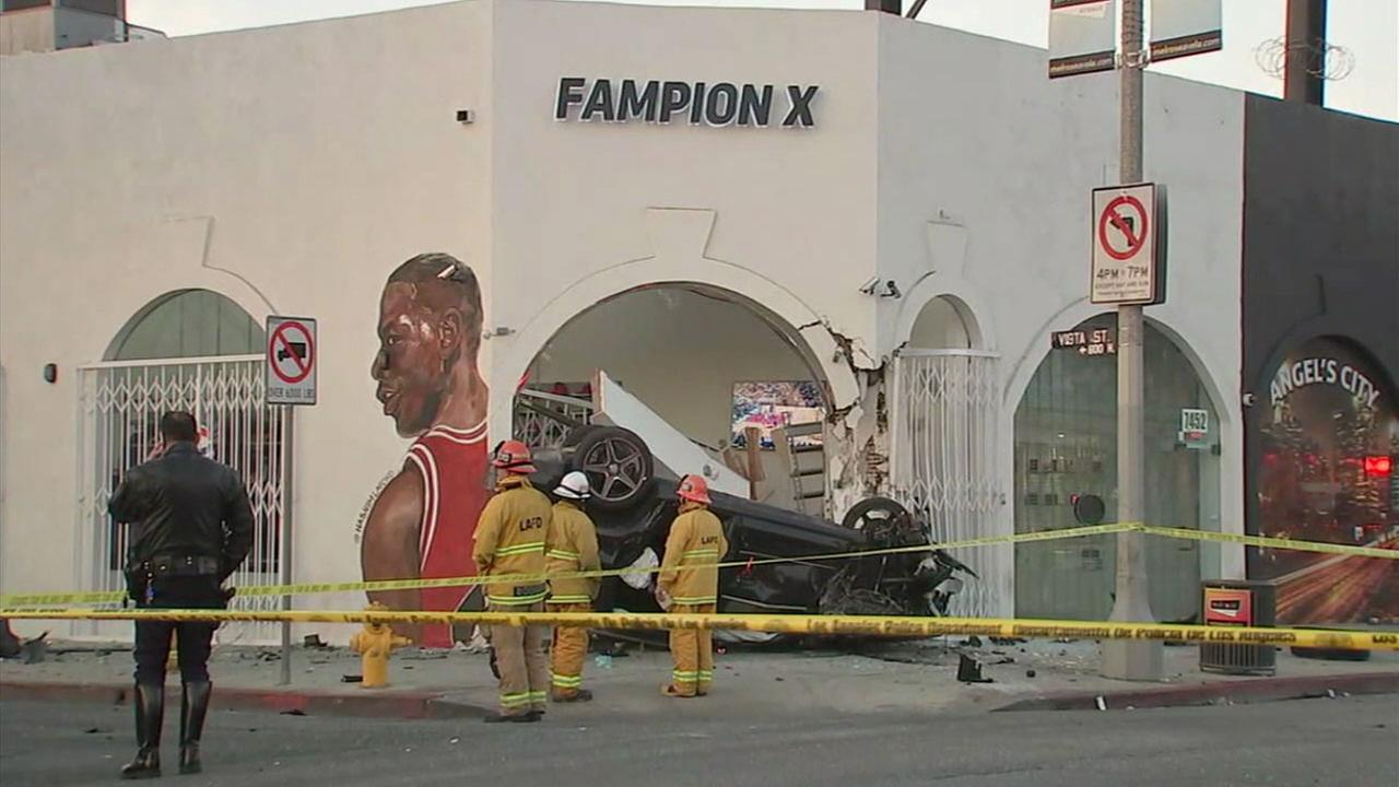 A mangled and upside down SUV is shown in front of a sports apparel store in Hollywood after the driver crashed into an Uber early Monday, Jan. 1, 2018.