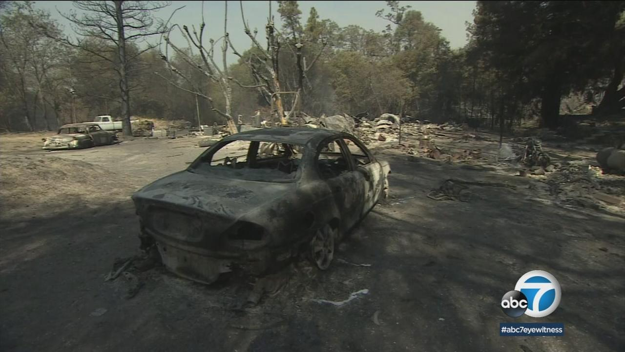A damaged vehicle and home are shown in Ventura after the Thomas Fire ravaged the area.
