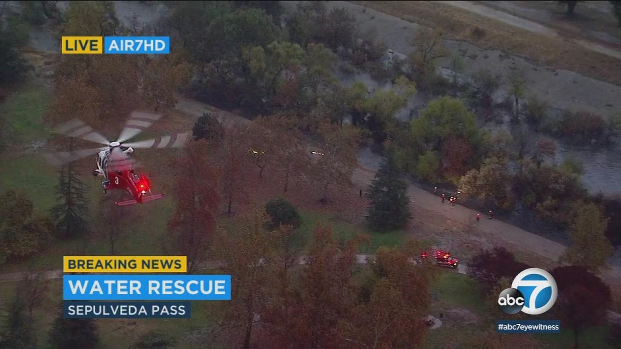 A swift-water rescue team plucked a man and his dog from the Los Angeles River in the Sepulveda Basin as a major winter storm brought torrential rain to the Southland.