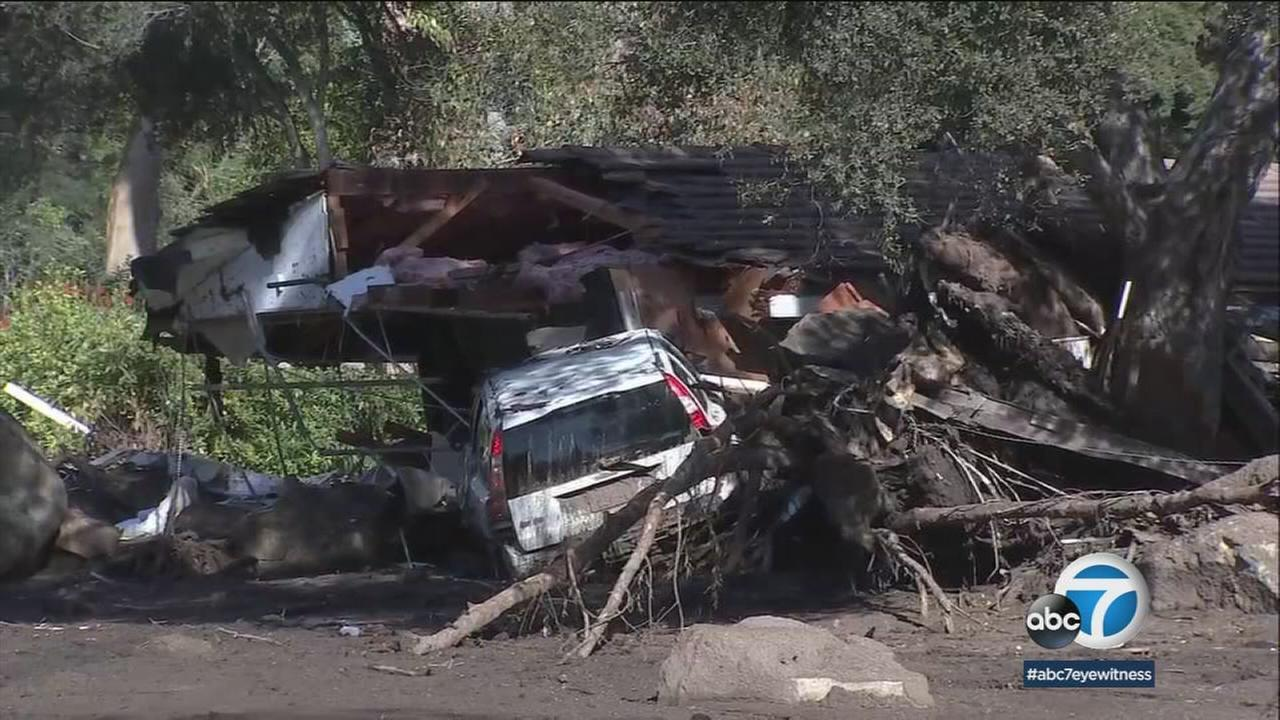 A mangled car is stuck between the pieces of a home and a tree after devastating mudslides swept through Montecito.