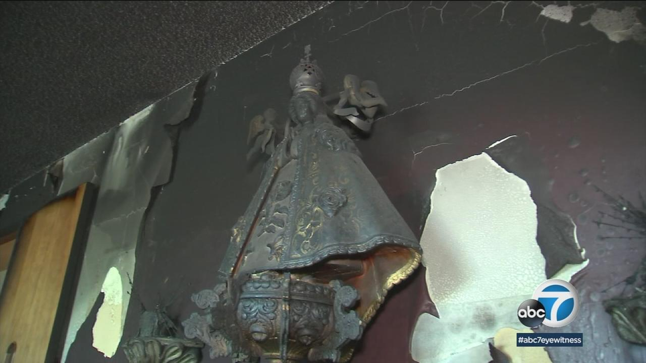 A Virgin Mary covered in soot and ash from an intentionally set fire is shown in a photo.