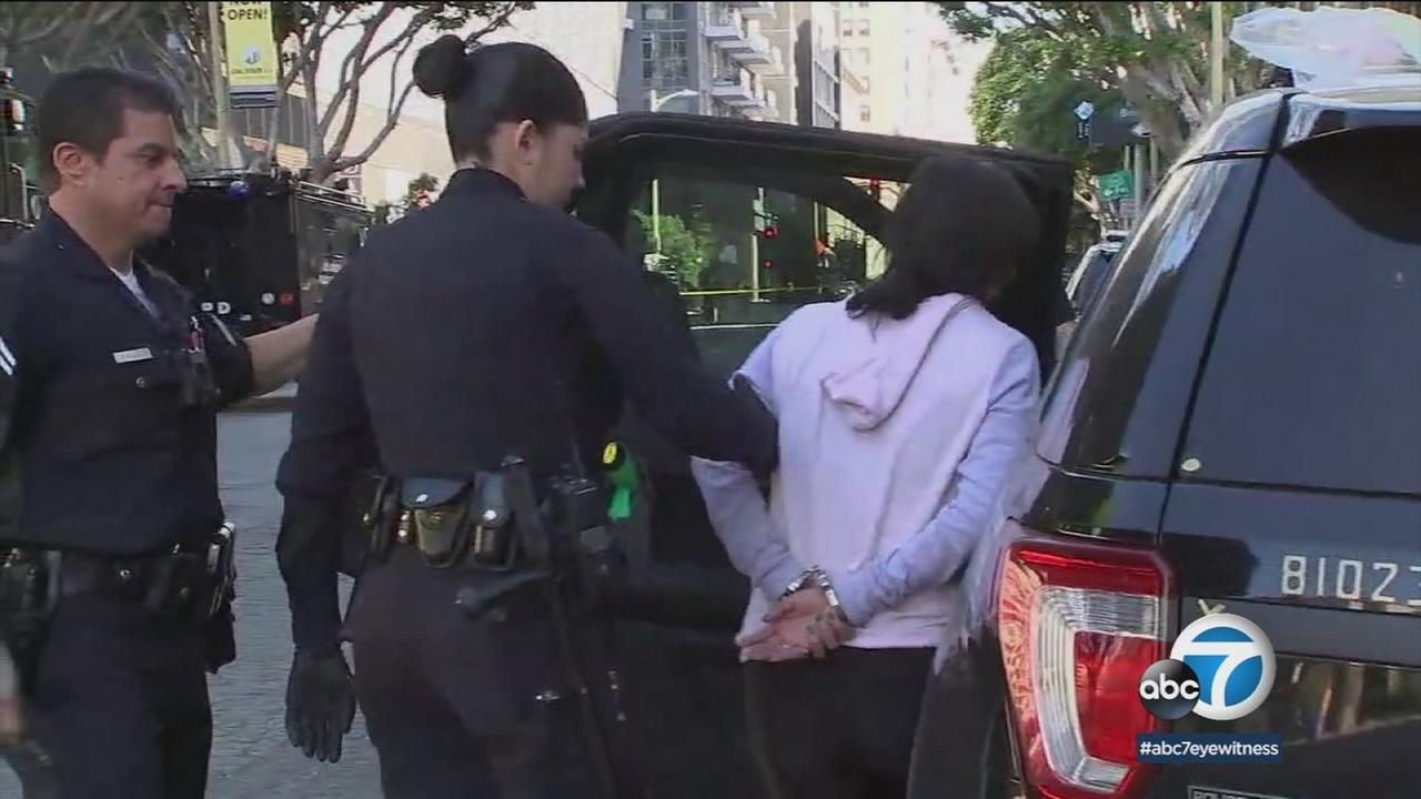 A woman is being placed into a patrol vehicle after being arrested during a report of a suspected assault prompted a SWAT response in downtown L.A. on Sunday, Jan. 28, 2018.