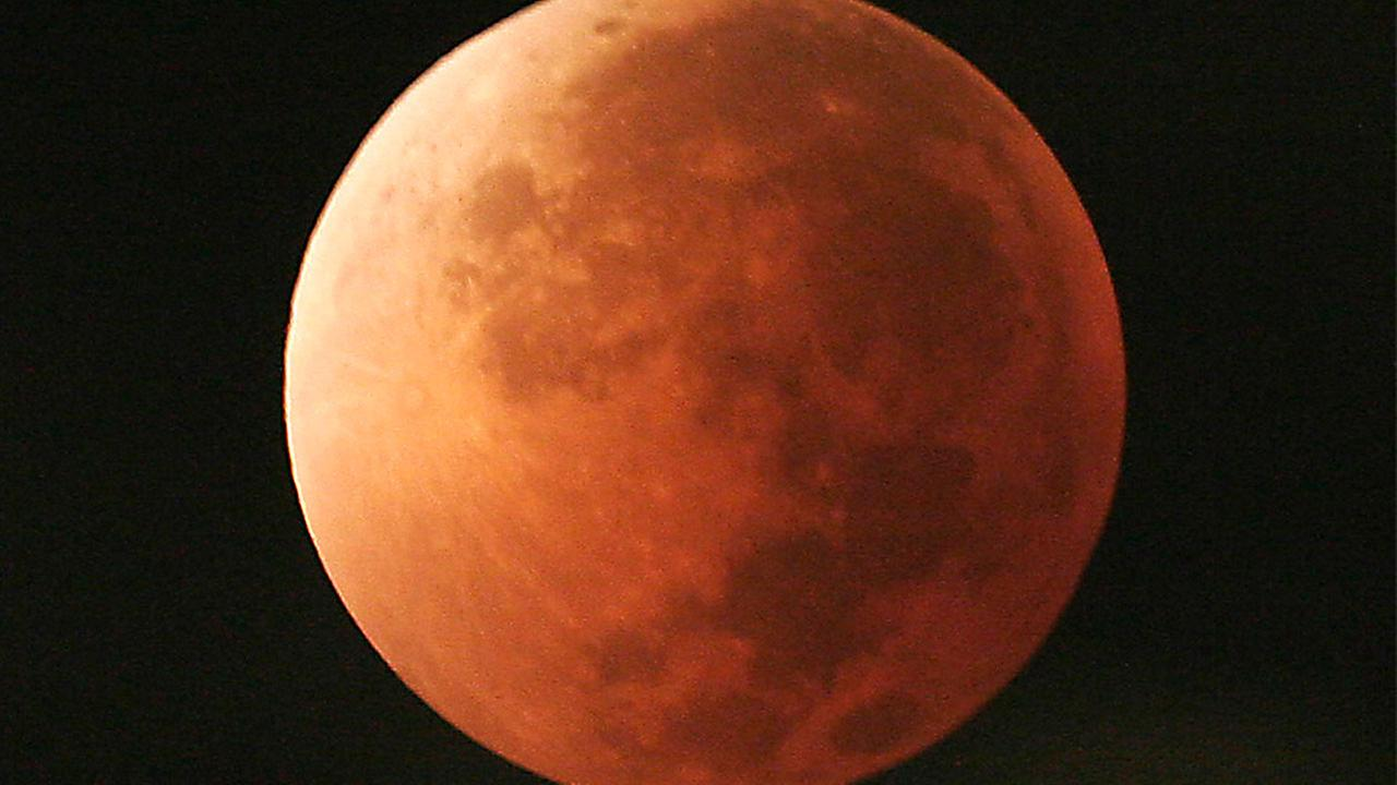 FILE - In this Aug. 28, 2007, file photo, the moon takes on different orange tones during a lunar eclipse seen from Mexico City.