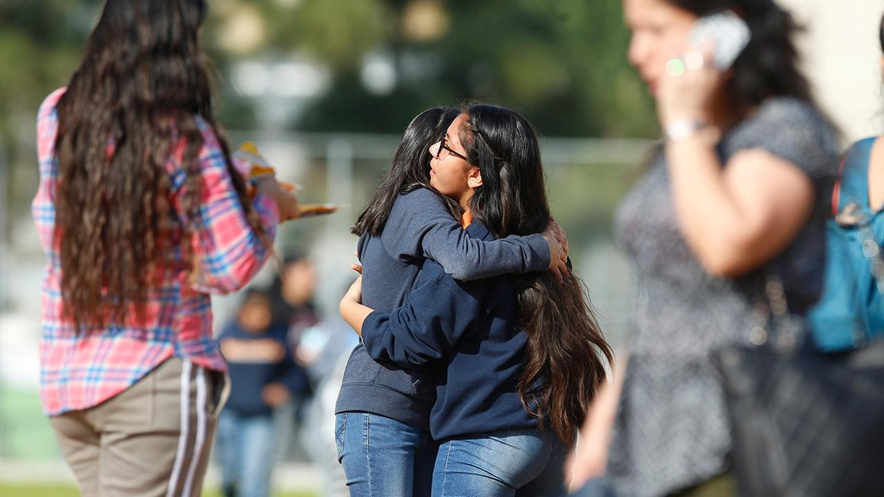 Students hug as people pick up students after a shooting at the Salvador B. Castro Middle School near downtown Los Angeles Thursday, Feb. 1, 2018.